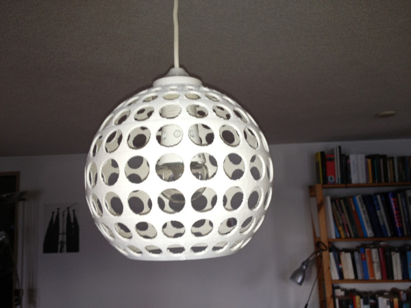 A white Ikea lampshade with holes in it.