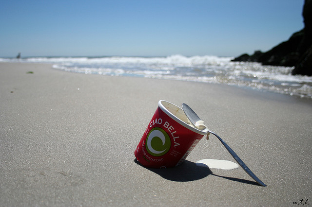 Picture of a tub of ice cream on a beach melting.