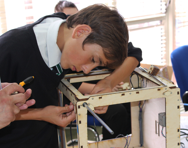 A student placing an axis rod on an Ultimaker one.
