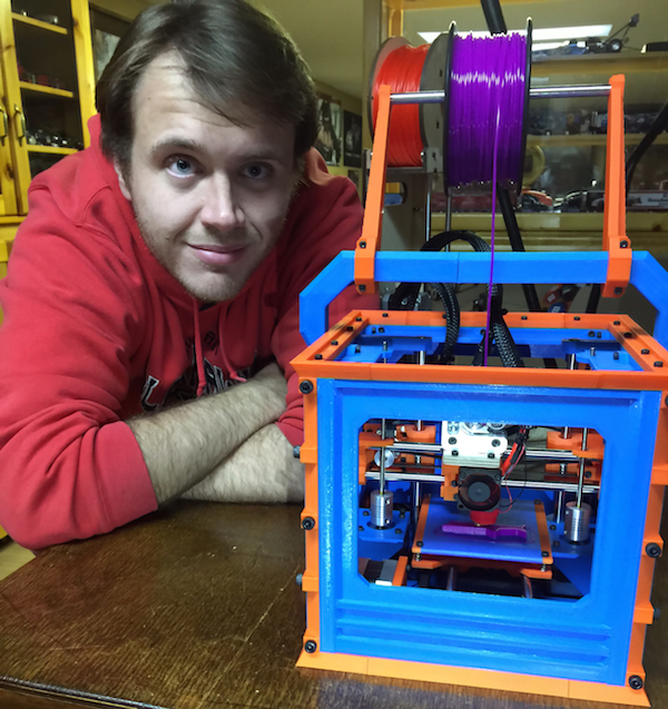 Ryan Adams leaning forward next to his MaplePrintMini 3D printer